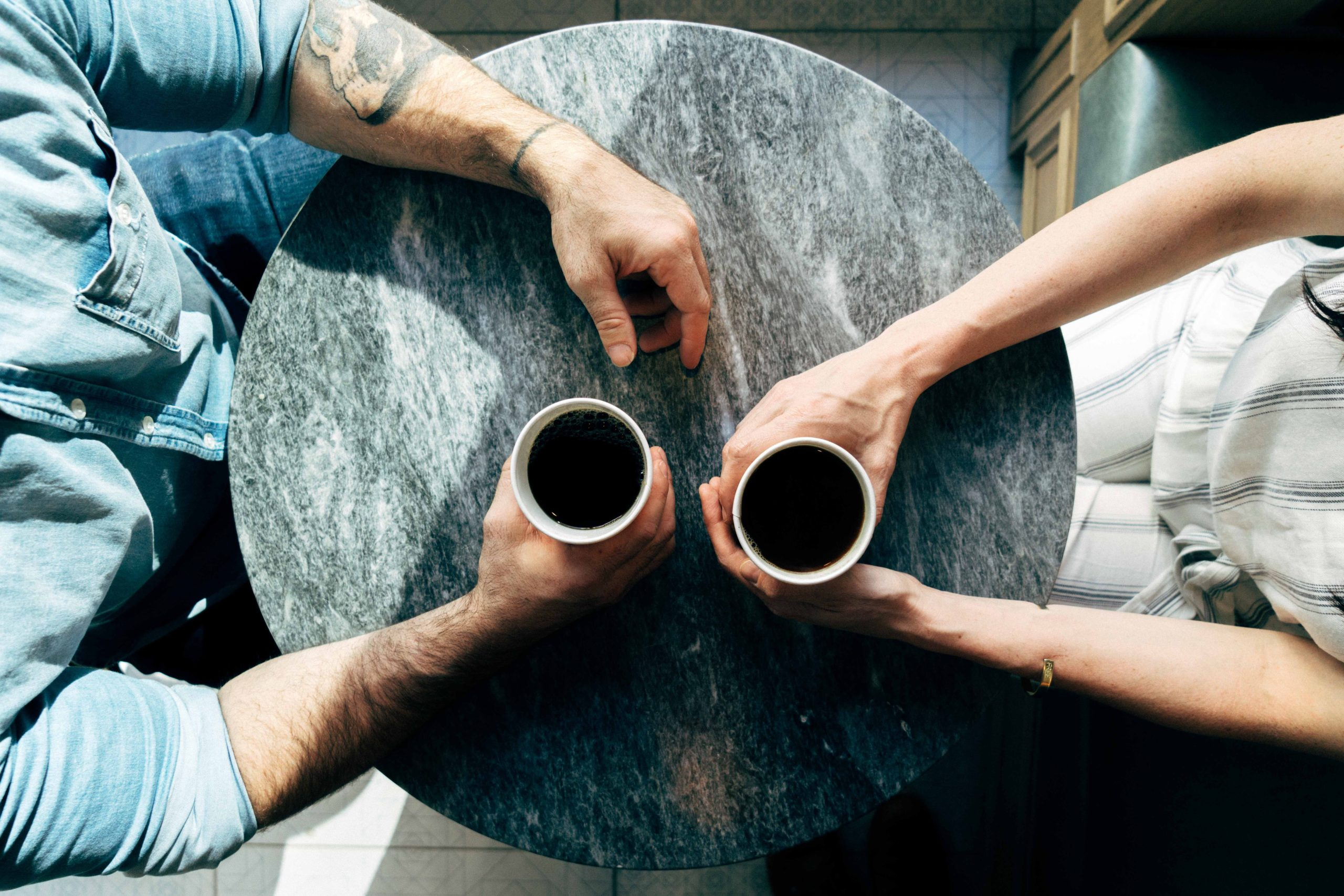 shot from above of two people holding coffees sitting at a table